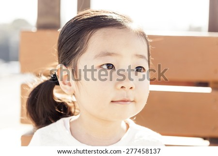 A girl(kid) wearing white dress(ice princess) sit down in a park bench with wonderful sunshine background at the spring. - stock photo