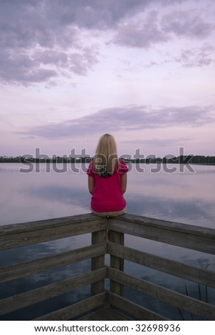 A girl looking at over a lake with a pink sunset. - stock photo
