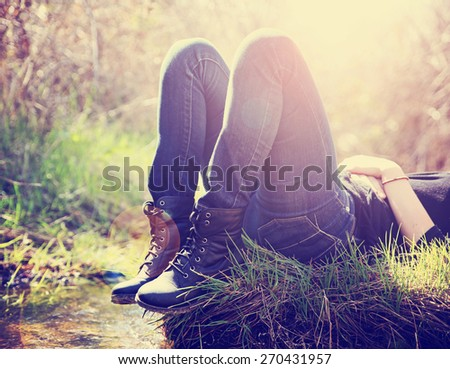 a girl lying on a small island in a stream with jeans and black combat boots on backlit with the setting sun toned with a retro vintage instagram filter effect app or action  - stock photo