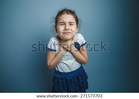 a girl of seven European appearance brunette holding hands by the throat on a gray background, choking, gasping - stock photo