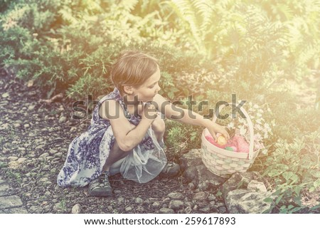 A girl on an egg hunt collects color dyed Easter eggs in her basket outdoors in a garden during the spring season.  Part of a series.  Filtered for a retro, vintage look. - stock photo