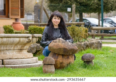 A girl posing and smiling behind a wood mushroom in a public park - stock photo