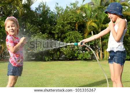 A girl pours water from a hose at my sister - stock photo