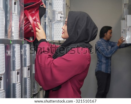 A girl putting her hand bag in a locker. - stock photo