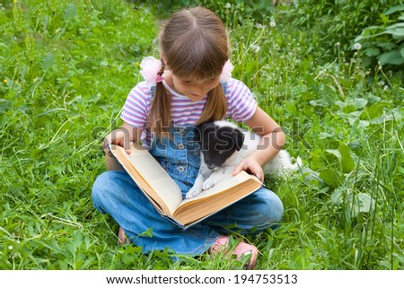 A girl reading  book with little puppy in garden - stock photo