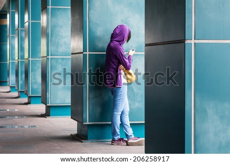a girl rest side by the pillar and playing her phone - stock photo