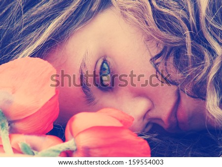a girl resting her head on a table with flowers vintage toned - stock photo