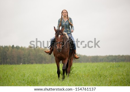 A girl rides a horse on the field - stock photo