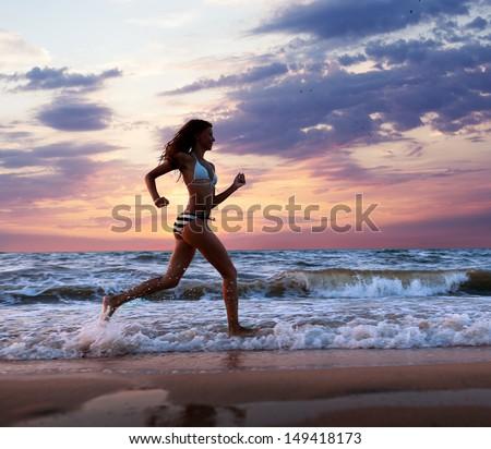 A girl runs along the beach - stock photo
