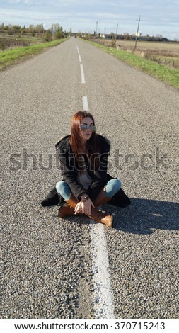 A girl sits on the road  - stock photo
