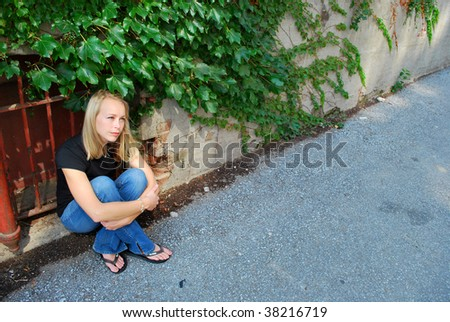 A girl sitting alone in a ally - stock photo