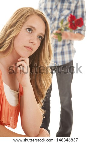 A girl sitting with a boy standing behind her holding three roses - stock photo