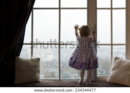 A girl standing near the window, watching  outside, where is the rainy day - stock photo
