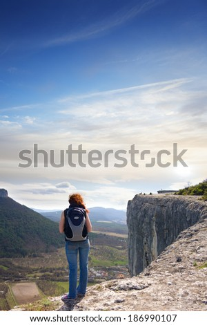 A girl standing on the edge of the high mountain and looking ahead - stock photo