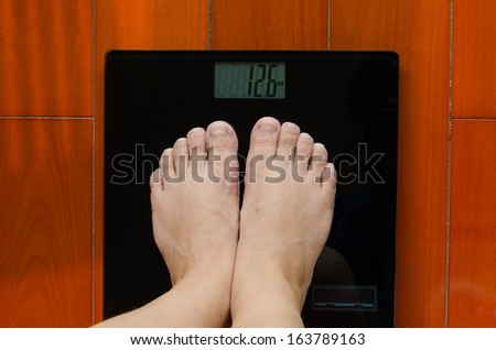 A girl standing on the weighing-machine to know how weight she is. this is part of the fit-keeping plan./Two feet on the weighing-machine - stock photo