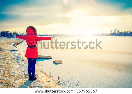 a girl stands near the edge of the river in winter with heaved up hands top - stock photo