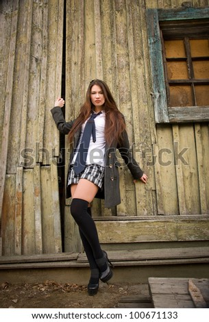 A girl stands near the old wall - stock photo