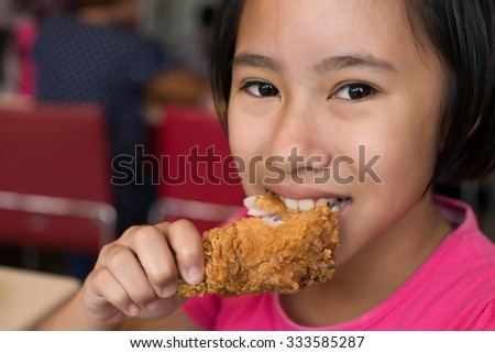 A girl tasted fried chicken - stock photo