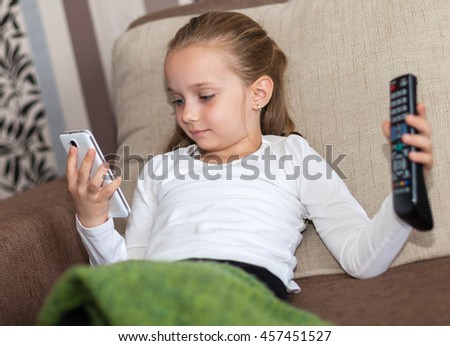 A girl undecided who can not choose between TV or phone - stock photo