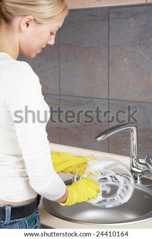 A girl washes a dish on a kitchen - stock photo
