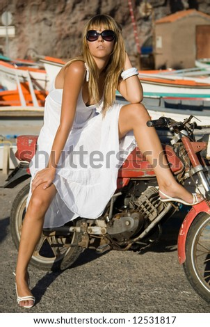 A girl wearing a fashion white dress with a motocycle - stock photo