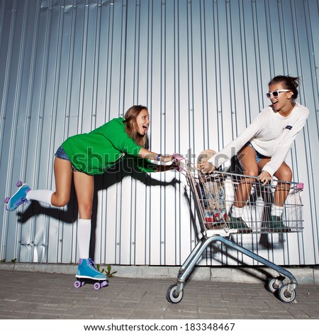 a girl wearing a green hoodie, sexy shorts, stockings and roller skates is pushing a supermarket trolley with a beautiful smiling girl standing in it - stock photo