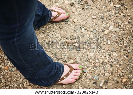 a girl wearing brown leather flip flop sandals on her feet with little rhinestone jewels on the straps with green nail polish and flowers painted on her big toes - stock photo