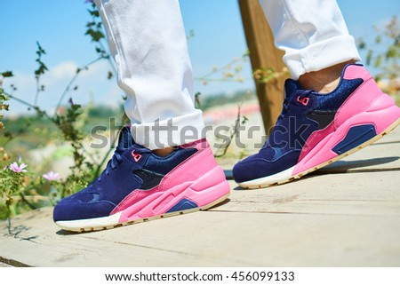 A girl wearing pink sports shoes and white pants, summer fashion trends, sporty look - stock photo