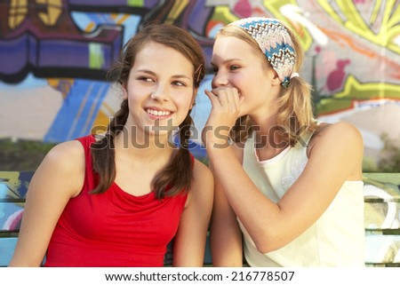 A girl whispering something into another girl's ear. - stock photo