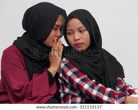 A girl whispering to a friend with white background. - stock photo