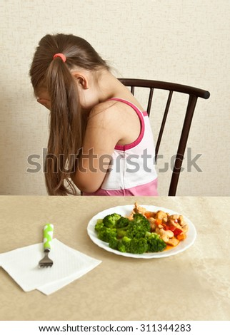 A girl with a bad mood sitting at the table - stock photo