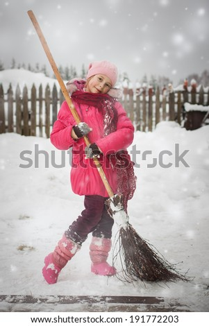 A girl with a broom outside the village. - stock photo