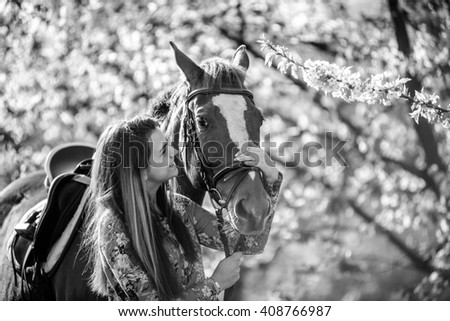 a girl with a horse in a dress standing in a garden - stock photo