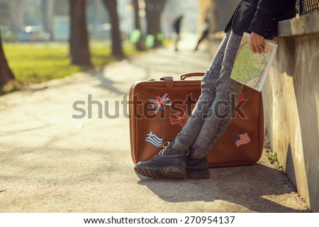 A girl with a map and suitcase. Focus on the boots. - stock photo