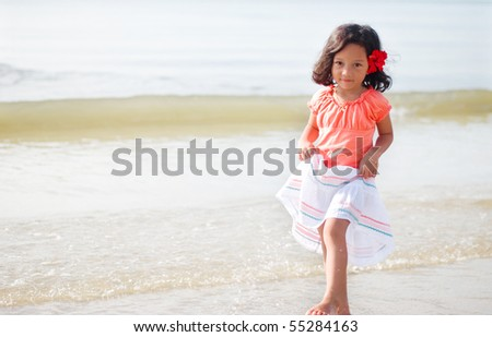 A girl with flower at the beach - stock photo