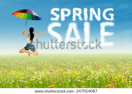 A girl with umbrella jumping beside of spring sale clouds - stock photo