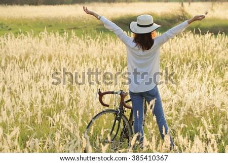 A girl with vintage bicycle at meadow in the early morning. Sun shine with golden light, silhouette back light on her body and grass flowers. Image create for people, healthcare, fashion and cosmetic. - stock photo
