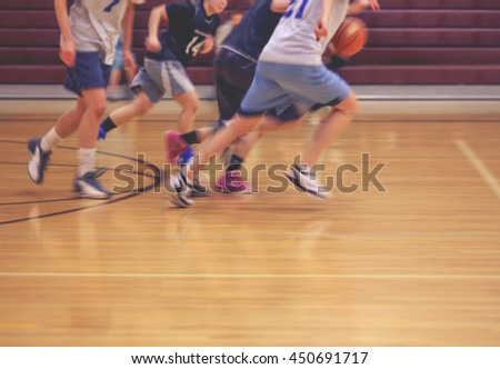a girls basketball team running up or down the court (no point of focus) toned with a retro vintage instagram filter effect app or action  - stock photo