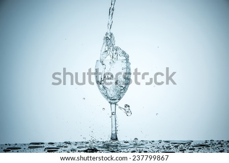 A glass being filled with water on white background - stock photo