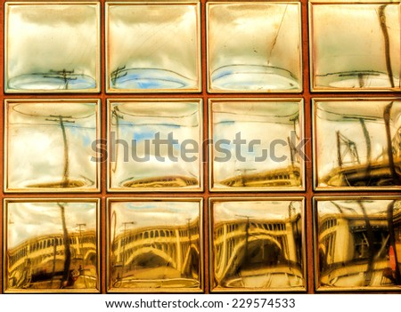 A glass-block window reflection provides a golden-toned view of Cleveland's Flats district - stock photo