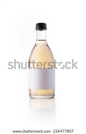 A glass bottle with liquor with blank label reflective bottom isolated white. - stock photo
