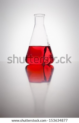 A glass bottle with red liquid in a laboratory - stock photo