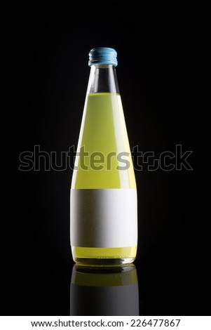 A glass bottle with yellow soft drink with blank label reflective bottom isolated black. - stock photo