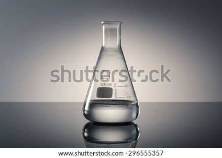 A glass Erlenmeyer flask with water(liquid, fluid) on the reflected black desk in the laboratory - stock photo