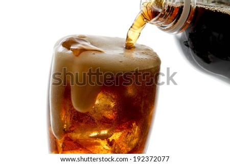 A glass filled with ice cubes and a frothy beverage. - stock photo