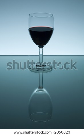A glass filled with red wine reflected in a mirror. The reflection shows an empty wine glass. - stock photo