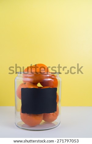 A glass jar full or oranges with a space to write your message on the chalkboard label - stock photo