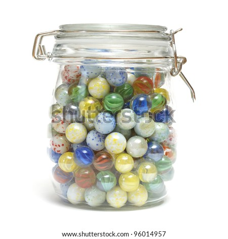 A glass jar is full of various marbles. - stock photo
