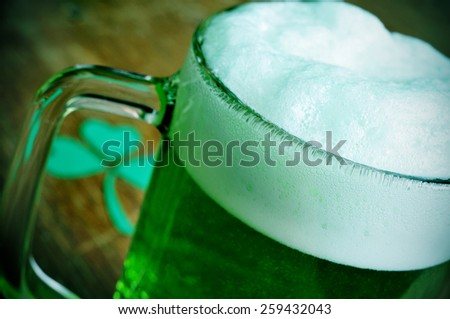 a glass mug with dyed green beer and a three-leaved shamrock on a wooden table, for saint patricks day - stock photo