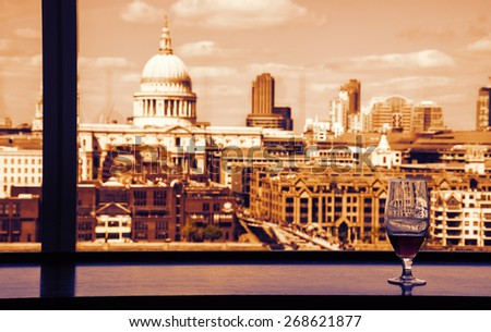 A glass of beer and a view from Tate Modern gallery's cafe on St Paul Cathedral with Millennium Bridge over Thames river. London, England. Reflections. Toned photo. - stock photo